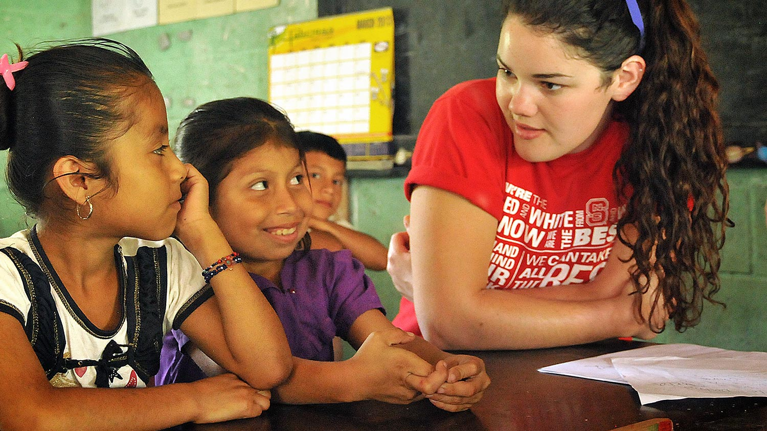 A female NCState student talking to young children during her peace corps mission.