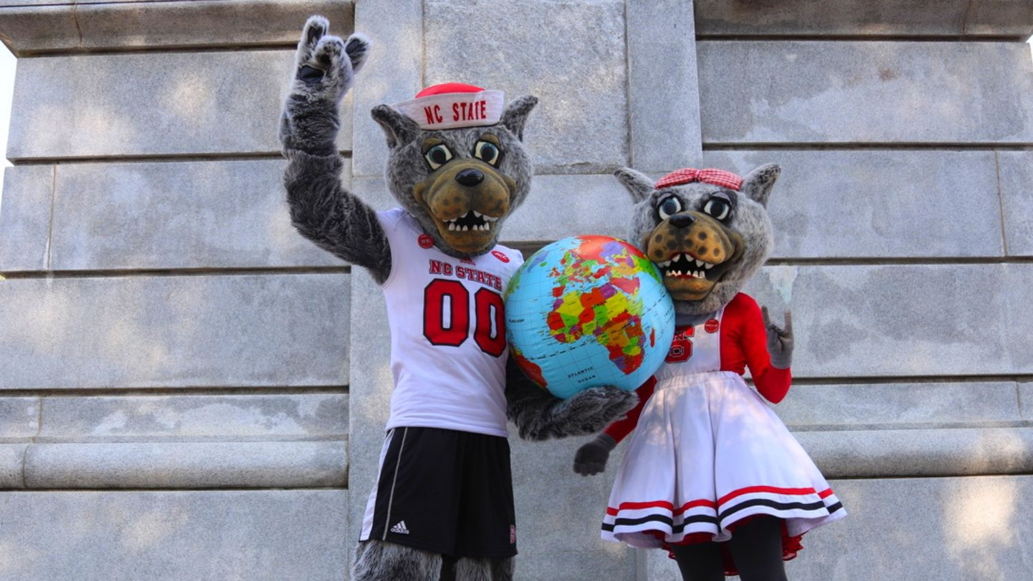 NCState's mascots, Mr and Mrs. Wuf, are holding a globe in front of the belltower.