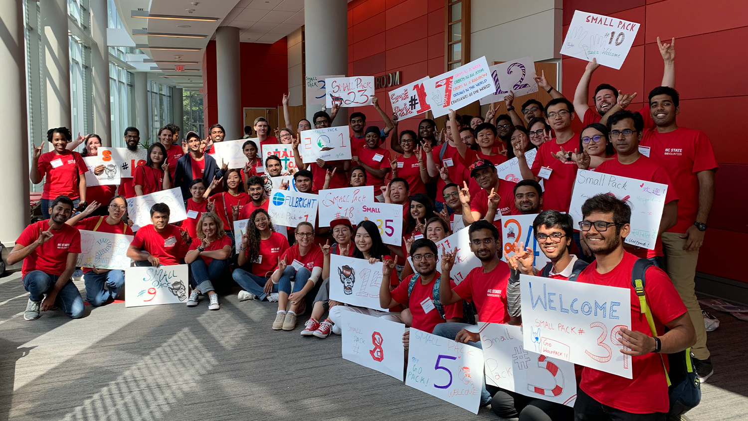 A group of international students volunteering as Small Pack Leaders are posing for a photo while holding up their group signs.