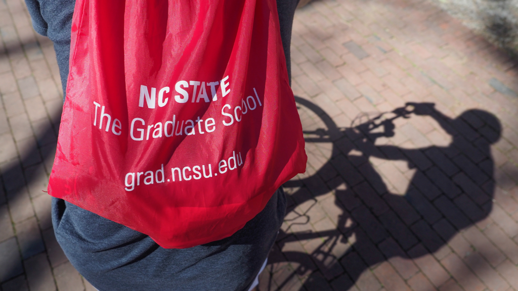 A close up photo of someone on a bike with a drawstring bag of The Graduate School.