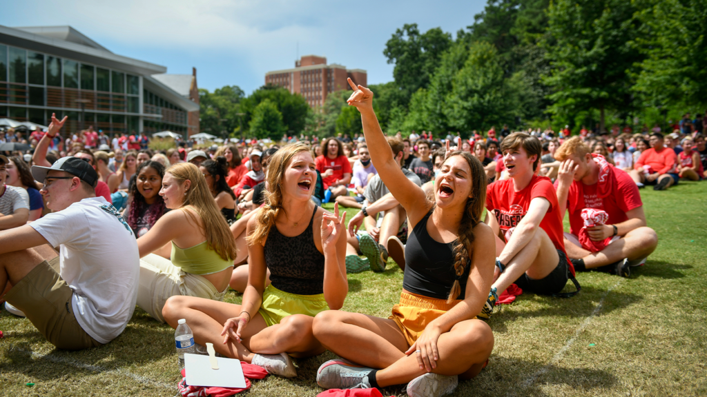 students sitting outside on grass during convocation.