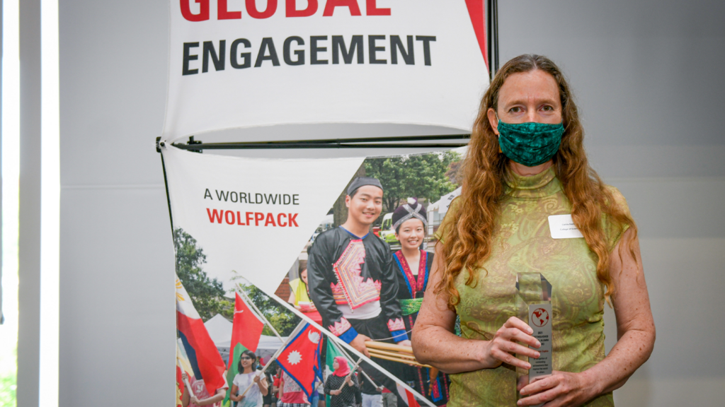 A white woman holding up her award (Distinguished Global Alumni Award) in front of a NCState Global backdrop.