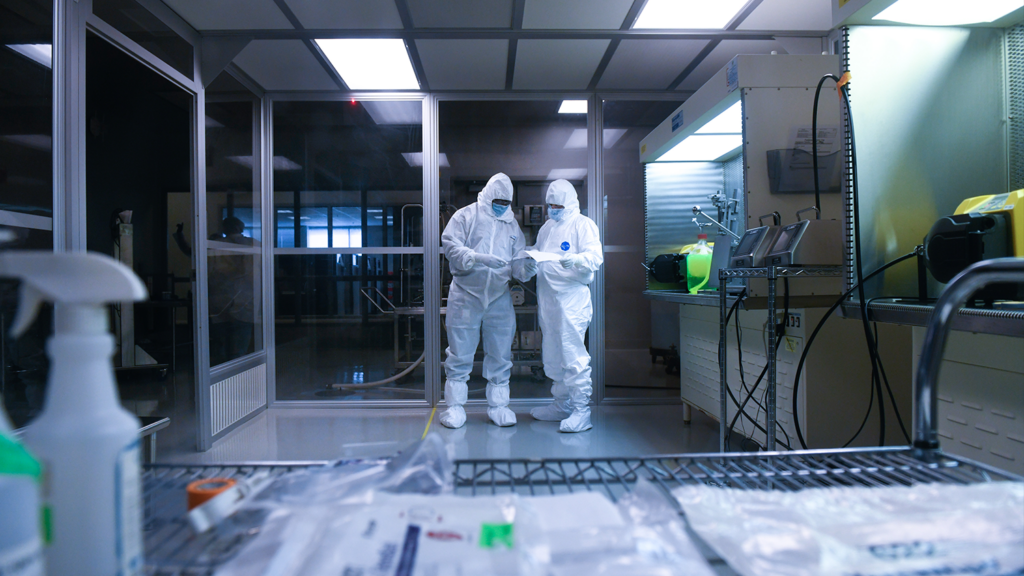 Two people in white protecttive gear and mask standing in a lab looking at paperwork.