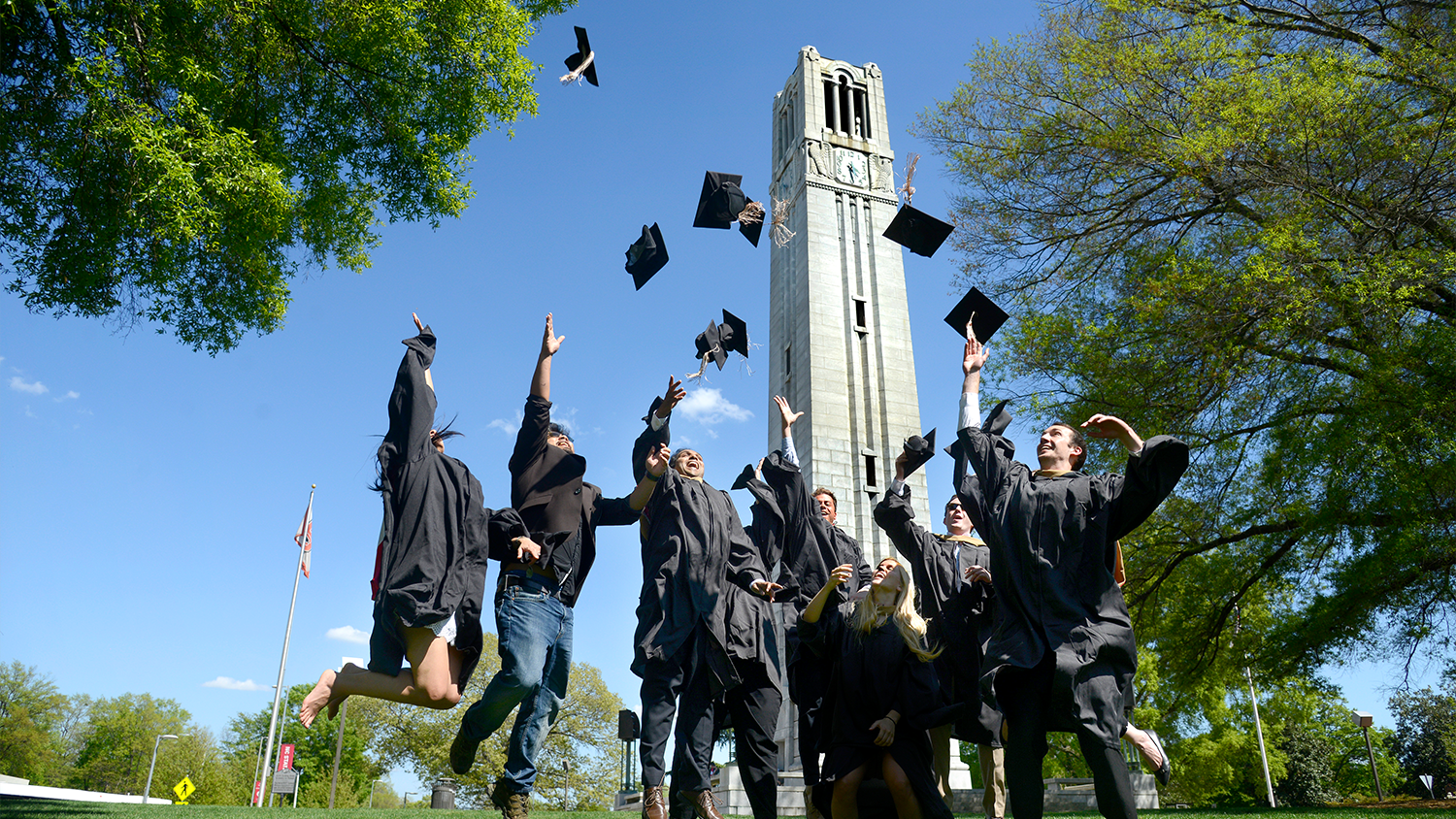 A group photo of Master students who are jumping for air in their black cap and gown in front of the NCState belltower.