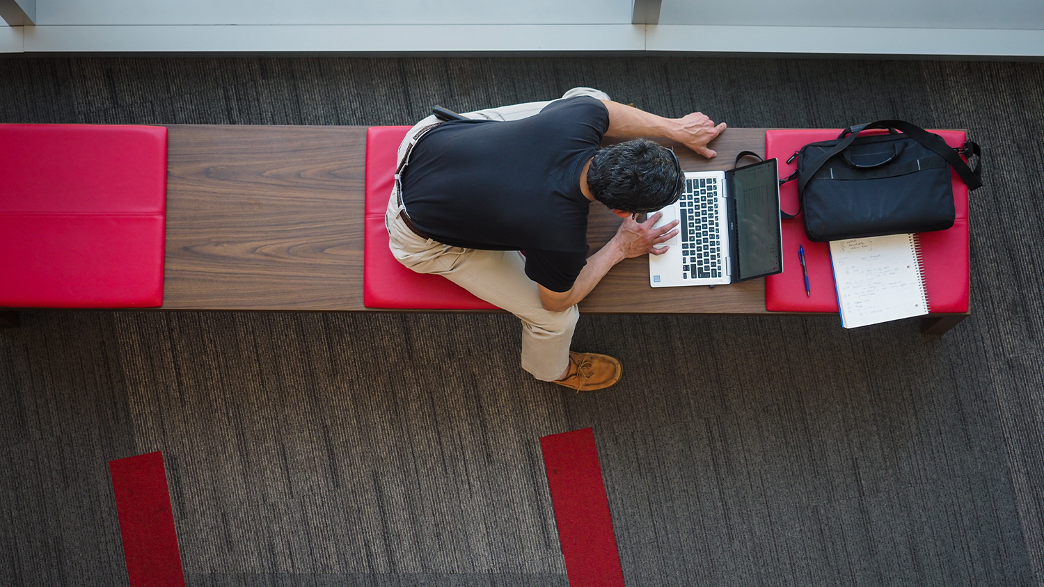 A faculty member is seen working on a laptop from an arial view.