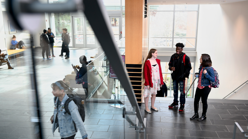 Students inside SAS Hall stopping for a quick group chat.