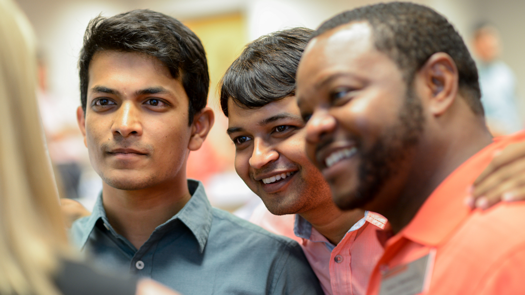 A close up shot of a group of three young men smiling.
