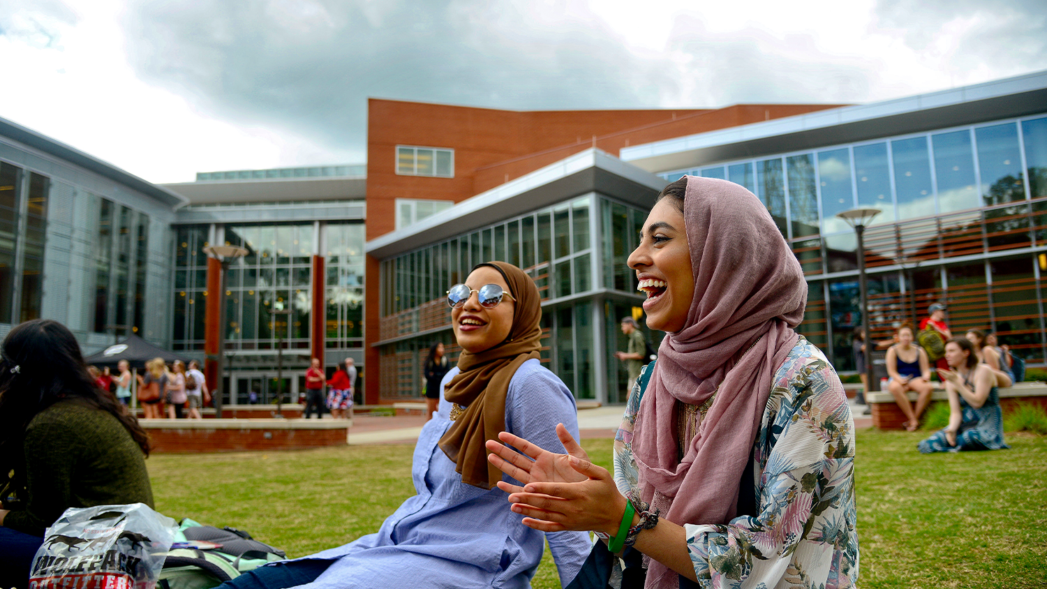 Two female students with head scarfs are sitting on grass smiling at each other. There are other students in the background.